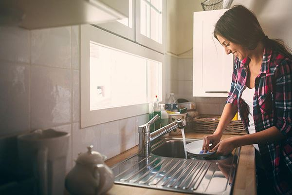Woman at sink cleaning dishes